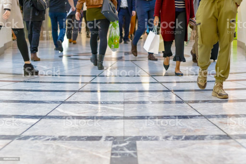 A modern floor with legs of a crowd walking in the background stock photo