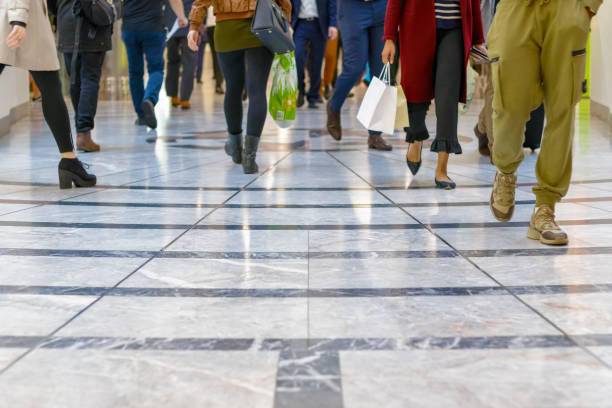 a modern floor with legs of a crowd walking in the background - people uk stock photos and pictures