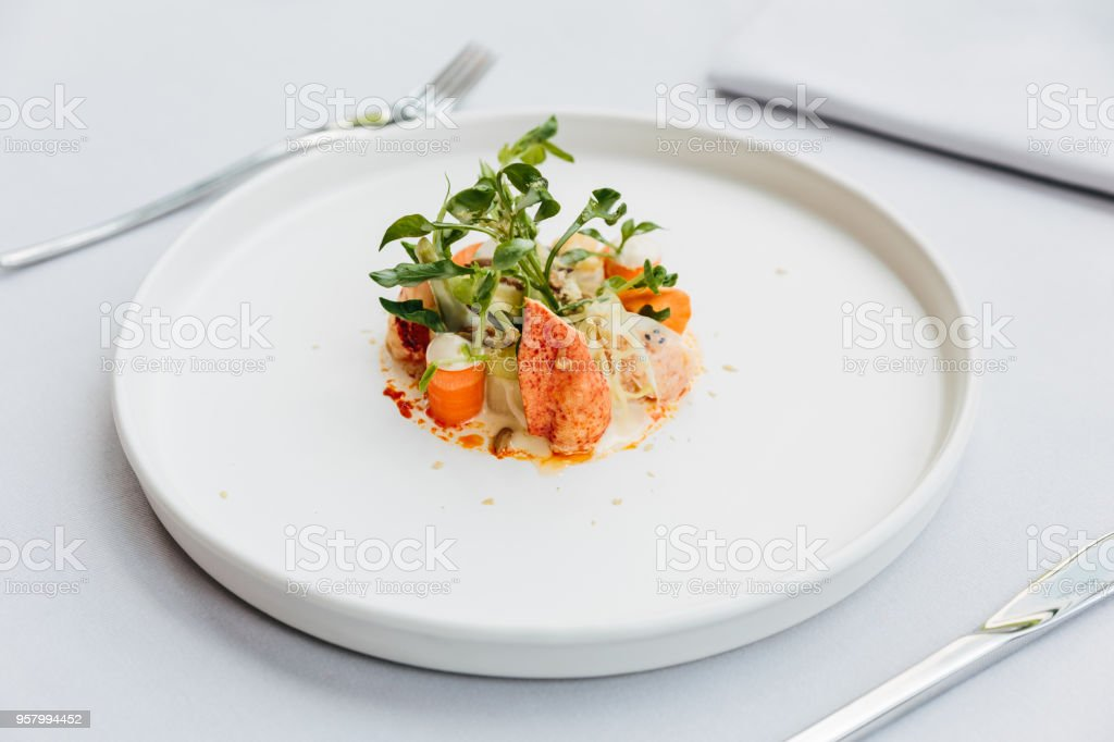 Modern French cuisine: Lobster tail salad including lobster, asparagus and roasted sunflower seeds with white sauce served in white plate. stock photo