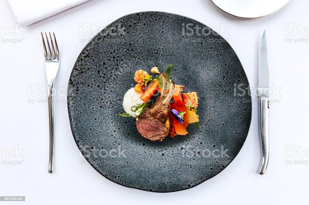 Cozinha francesa moderna: pescoço de cordeiro assado & cremalheira serviram com curry de cenoura, amarelo, servido na chapa de pedra preta com garfo e faca. - foto de acervo