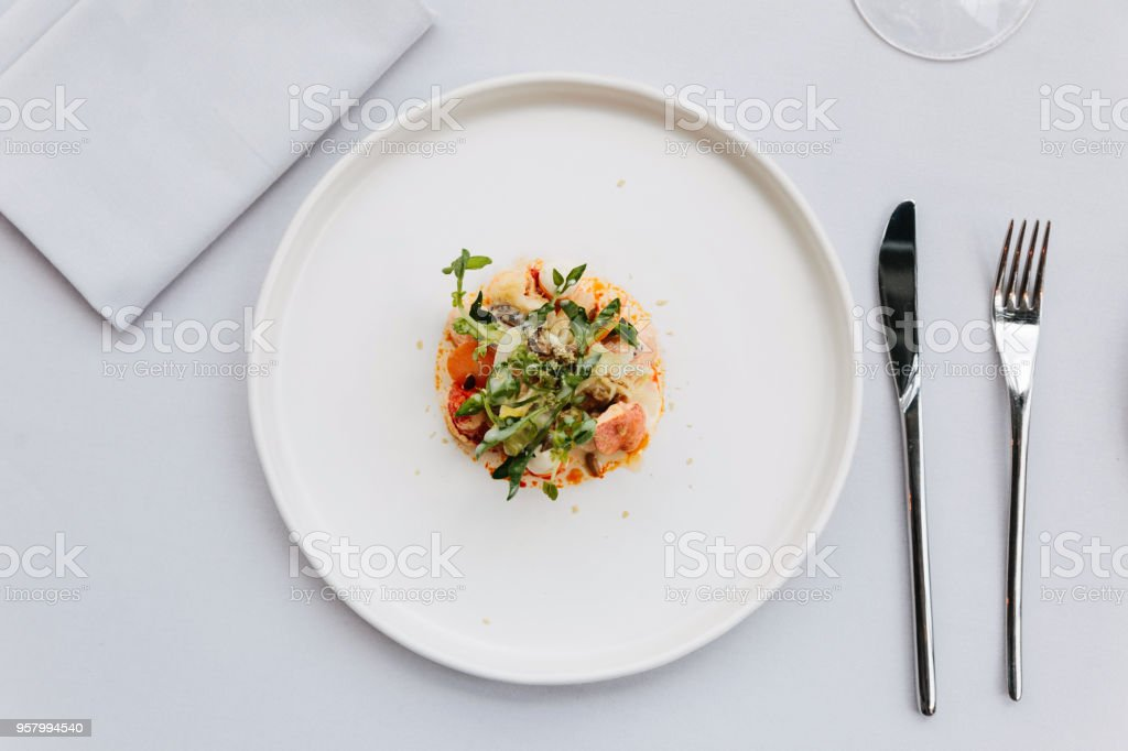 Modern French cuisine: Top view of lobster tail salad including lobster, asparagus and roasted sunflower seeds with white sauce served in white plate. stock photo