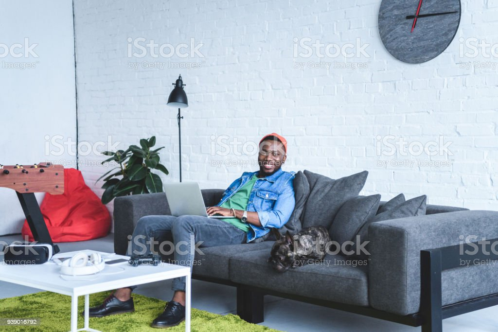Modern gadgets on table in front of african american man working on laptop and sitting on sofa by French bulldog stock photo
