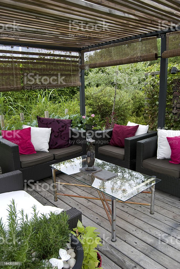 Modern garden with a pergola and wicker sofa royalty-free stock photo