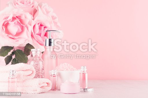 1056636898 istock photo Modern gentle girlish bathroom decor - cosmetics for bath and spa, bouquet of roses, bath accessories on soft white wooden table, pastel pink wall, closeup. 1154015158