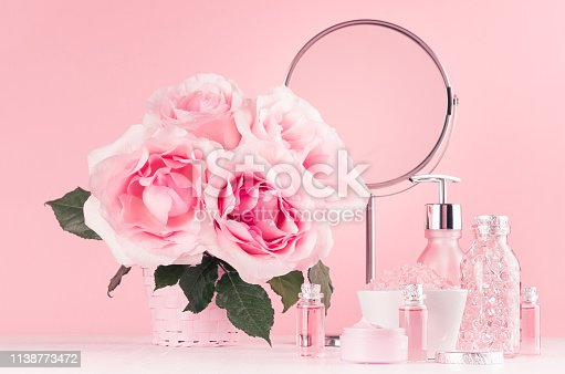 1056636898 istock photo Modern gentle girlish bathroom decor - cosmetics for bath, spa, bouquet of roses, round mirror, bath accessories on soft white wooden table, pastel pink wall. 1138773472