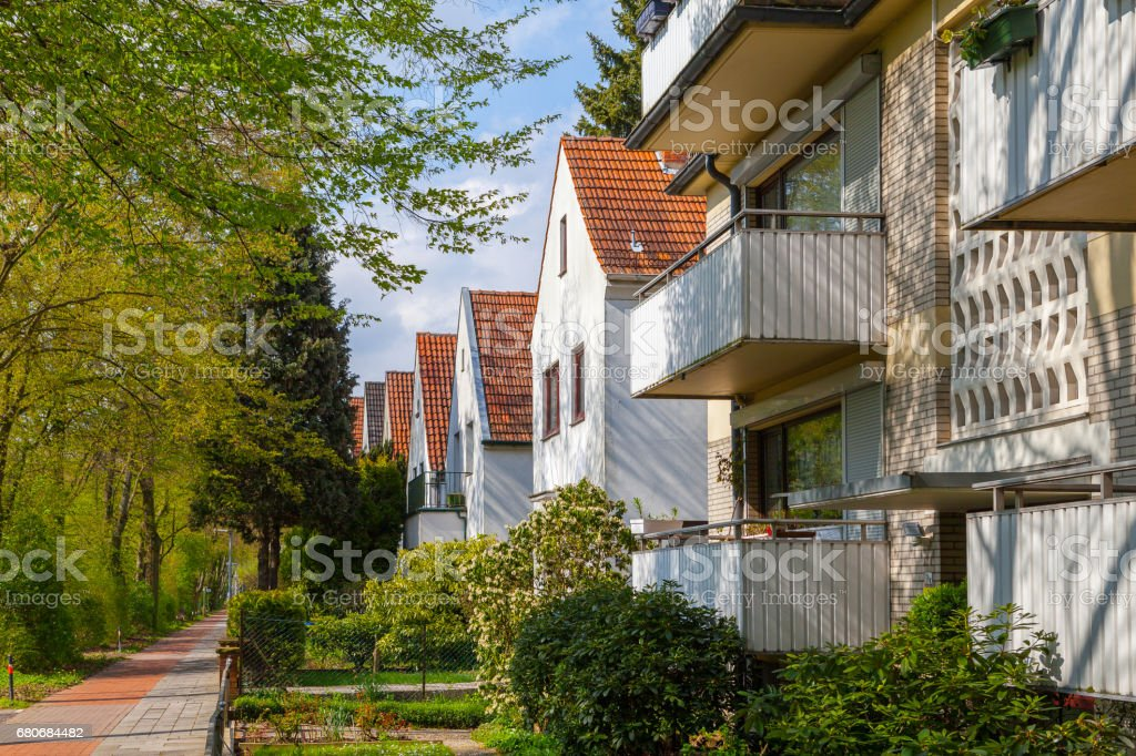 Modern german street with white stoned houses with tiled roofs. Sunny day and green alley. stock photo