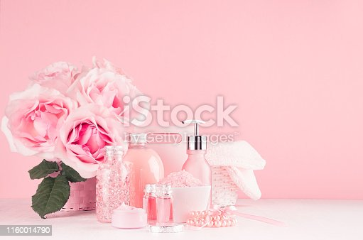 847096968 istock photo Modern girlish dressing table with pink cosmetics products, accessories and roses bouquet on soft white wood table, copy space. 1160014790