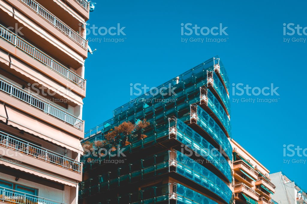 modern glass apartment building with big balcony between two older...