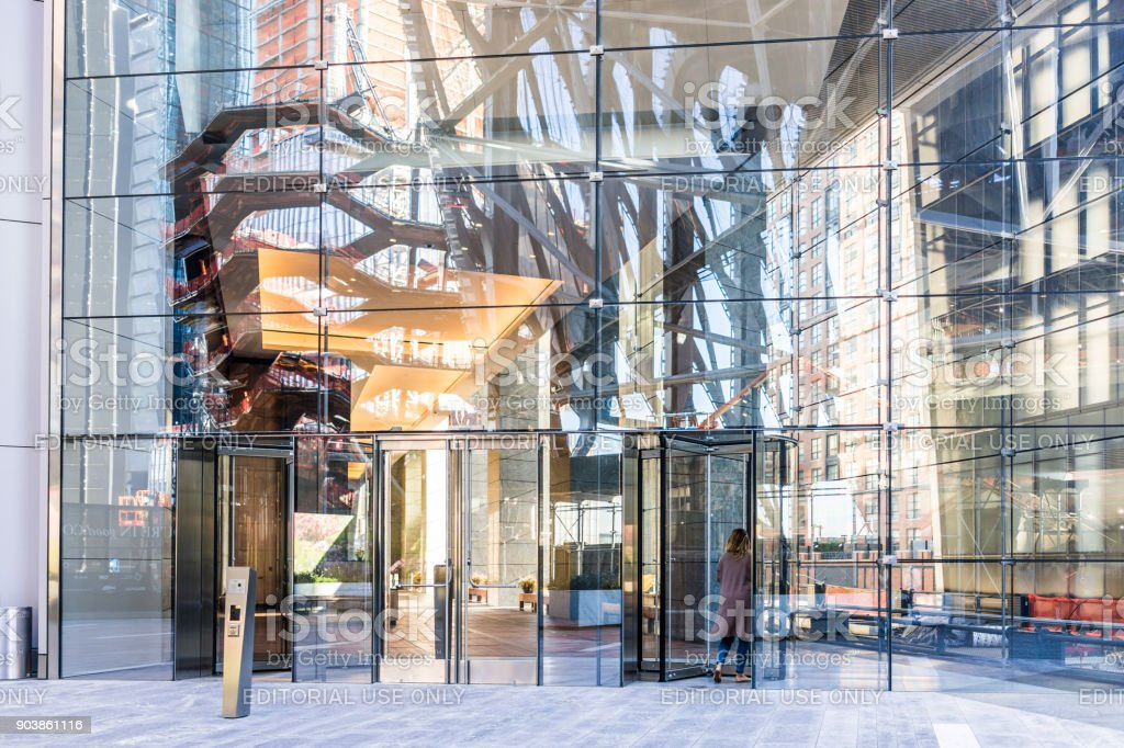 NYC modern glass building entrance with woman walking inside in Chelsea West Side by Hudson Yards, corporate business mall stock photo