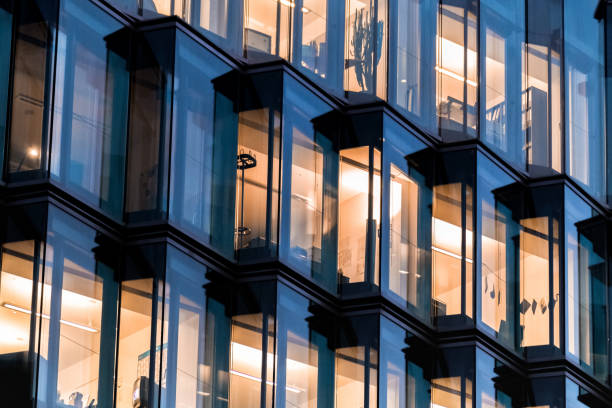 modern glass facade of office building in berlin at night stock photo