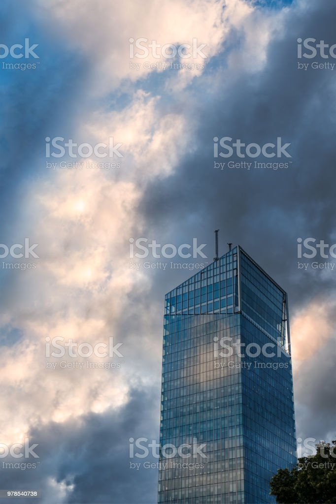 Modern glass office building against dramatic blue and yellow sky. stock photo