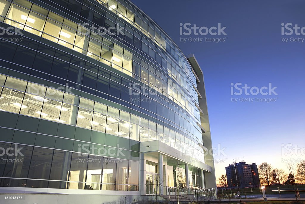 Modern glass office building at sunset stock photo