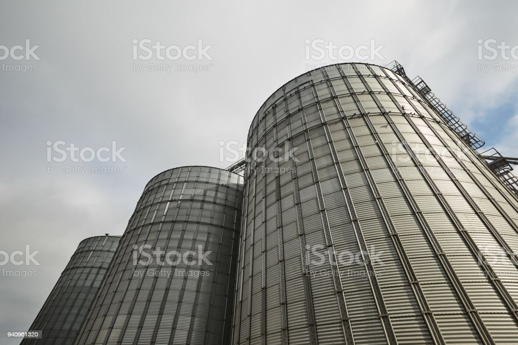 Modern grain terminal. Metal tanks of elevator. Grain-drying complex construction. Commercial grain or seed silos at seaport. Steel storage for agricultural harvest stock photo