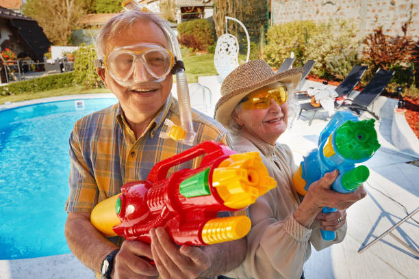 Modern grandmother grandfather and have fun playing with  water gun. stock photo