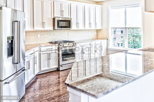 istock Modern gray, brown kitchen features front cabinets with granite countertops and tile backsplash with island and window 861060472
