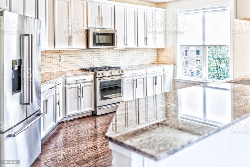Modern gray, brown kitchen features front cabinets with granite countertops and tile backsplash with island and window stock photo