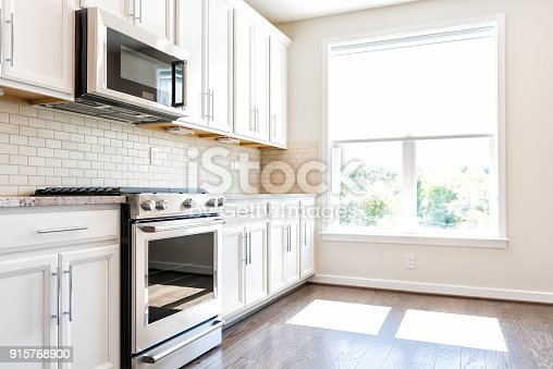 istock Modern gray, brown neutral kitchen features front cabinets with granite countertops and tile backsplash, window in contemporary home, house, apartment 915768900