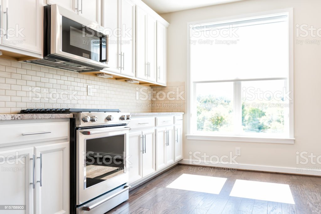 Modern gray, brown neutral kitchen features front cabinets with granite countertops and tile backsplash, window in contemporary home, house, apartment stock photo