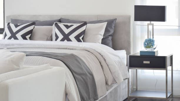 Modern Gray tone bedding and bedside table and lamp in black stock photo