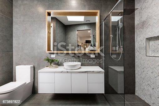 istock Modern grey designer bathroom with herringbone shower tiling 673897822