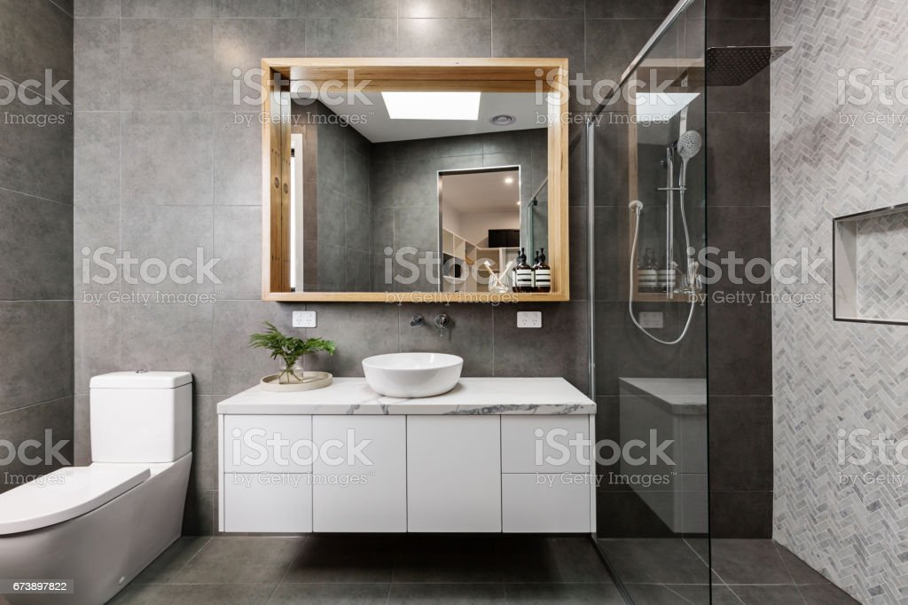 Modern grey designer bathroom with herringbone shower tiling stock photo