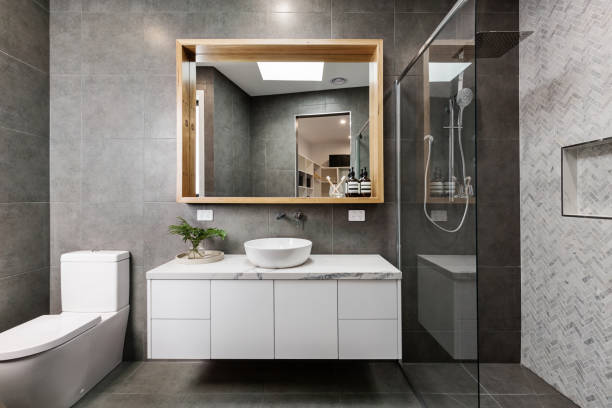 modern grey designer bathroom with herringbone shower tiling - bathroom renovation stock photos and pictures