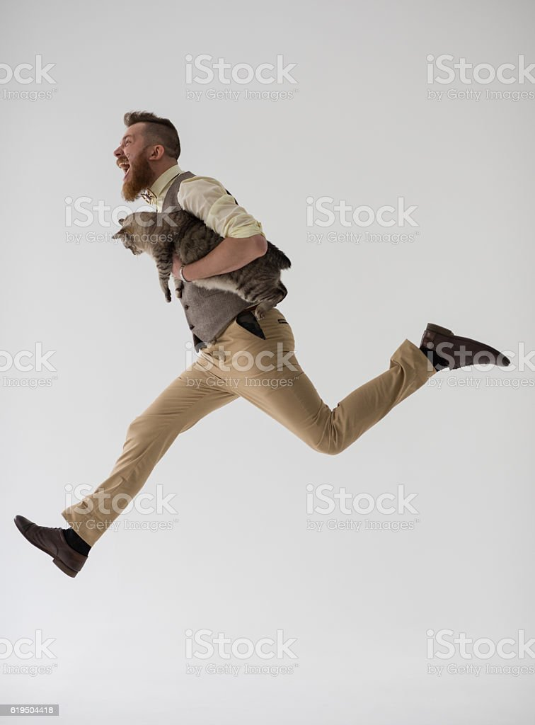Modern groom jumping with his cat stock photo