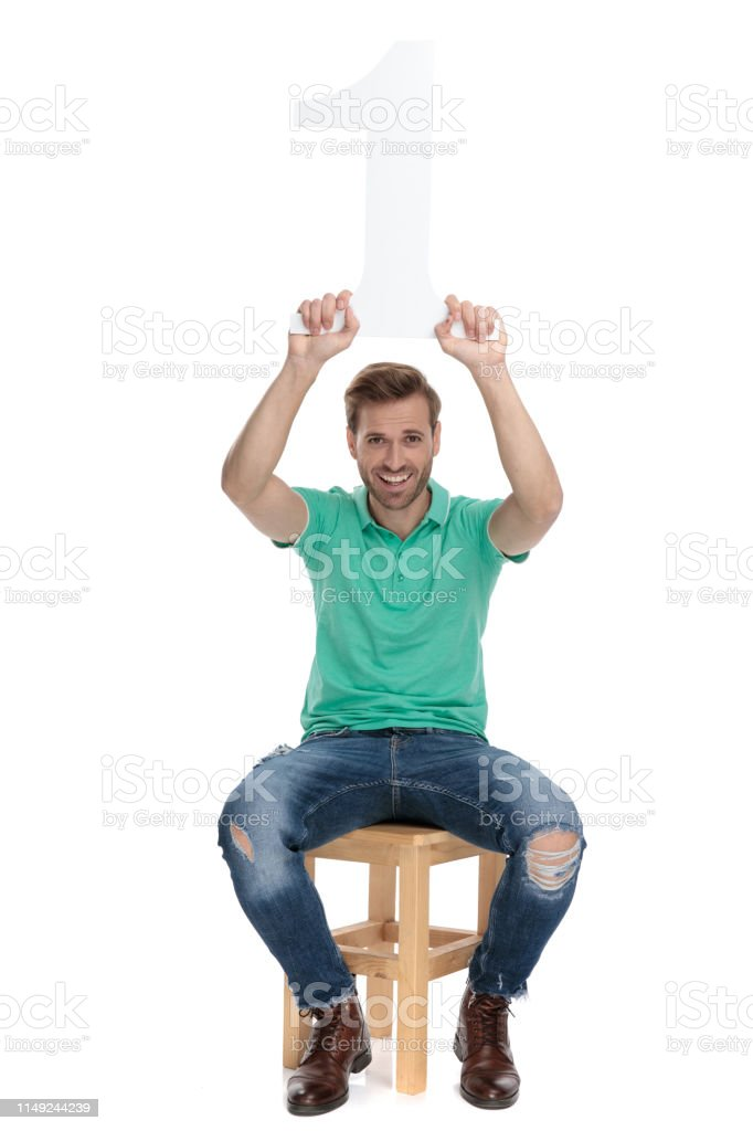 modern guy holds number one sign up in the air stock photo