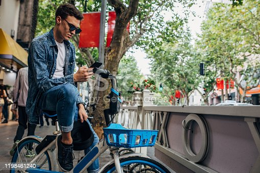 Handsome young man is sitting on a bicycle and text messaging.