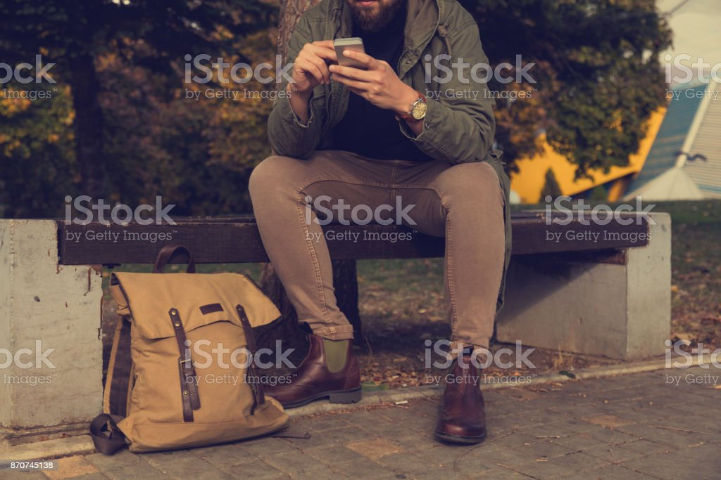 Modern guy sitting on the bench and texting on his cellphone. stock photo