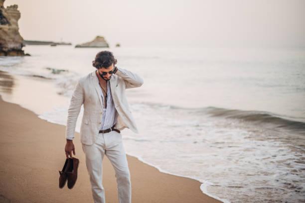 Modern guy taking a walk on the beach stock photo
