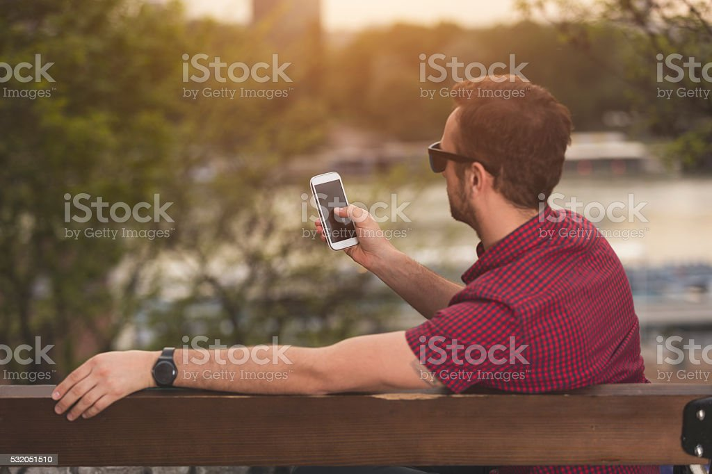 Modern guy using cellphone outdoors. stock photo