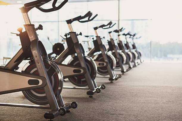 Modern gym interior with equipment, fitness exercise bikes Modern gym interior with equipment. Row of training exercise bikes detail, backlight. Healthy lifestyle concept exercise machine stock pictures, royalty-free photos & images