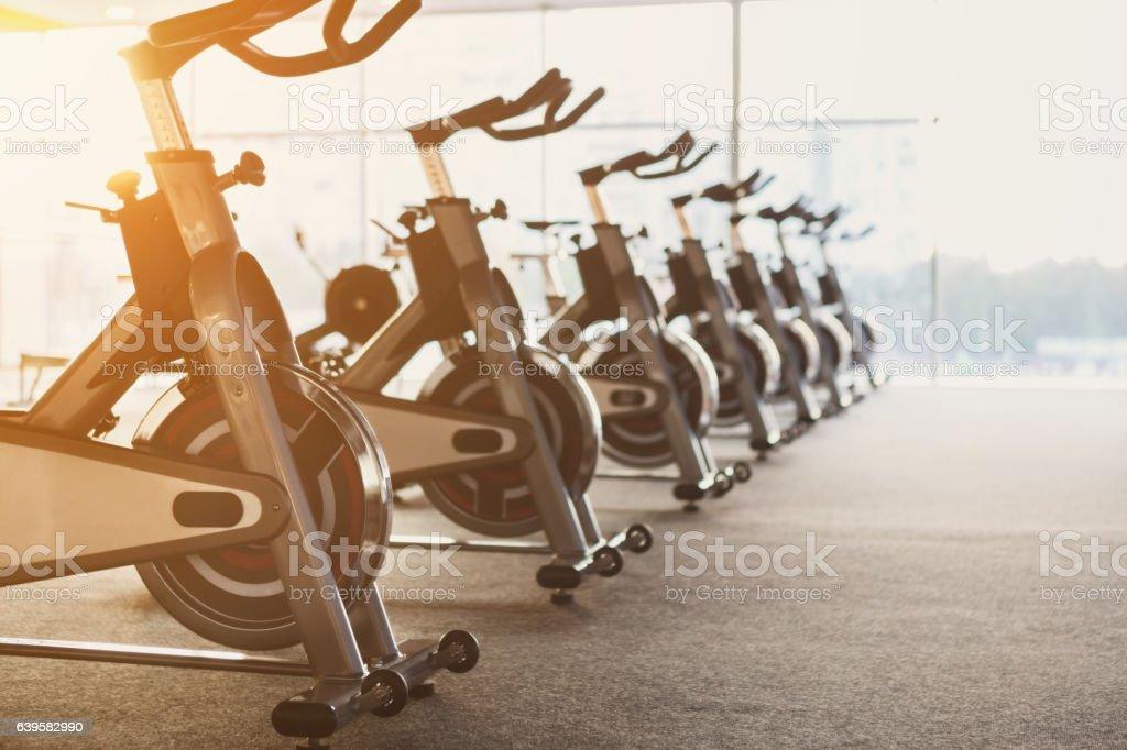 Modern gym interior with equipment, fitness exercise bikes foto de stock libre de derechos