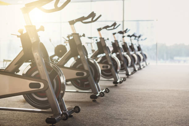 Modern gym interior with equipment, fitness exercise bikes Modern gym interior with equipment. Fitness club with row of training exercise bikes. Healthy lifestyle concept exercise bike stock pictures, royalty-free photos & images