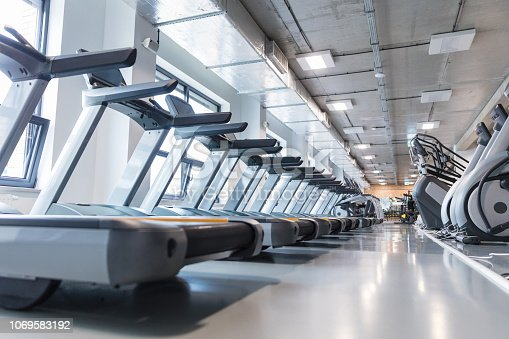 Fitness gym club with row of treadmills and elliptical trainers for fitness cardio training. Modern gym interior with equipment.