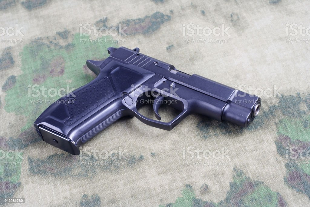 modern handgun on camouflage background stock photo