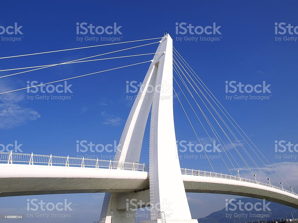 Modern hanging white bridge on a clear day stock photo