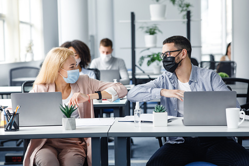 Modern contactless high five at work after lockdown and new normal. Happy millennial man and woman in protective masks touch their elbows at workplace with laptops and antiseptics in office