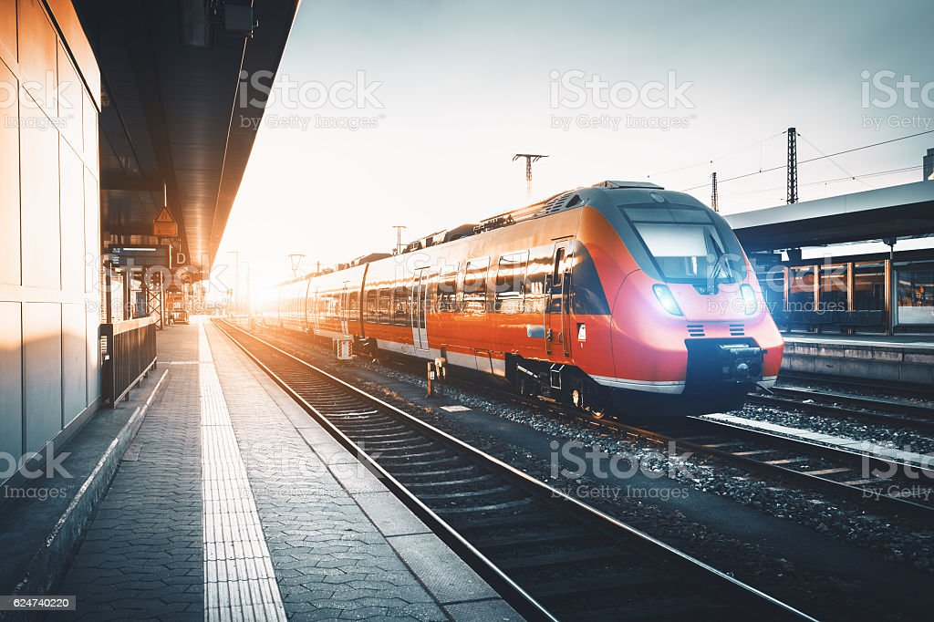 Modern high speed red commuter train at the railway station Modern high speed red commuter train at the railway station at sunset. Turning on train headlights. Railroad with vintage toning. Train at railway platform. Industrial landscape. Railway tourism Blurred Motion Stock Photo