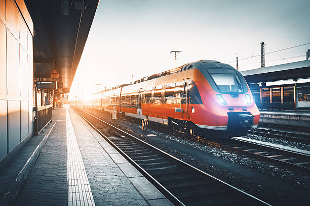 modern high speed red commuter train at the railway station - train stock photos and pictures