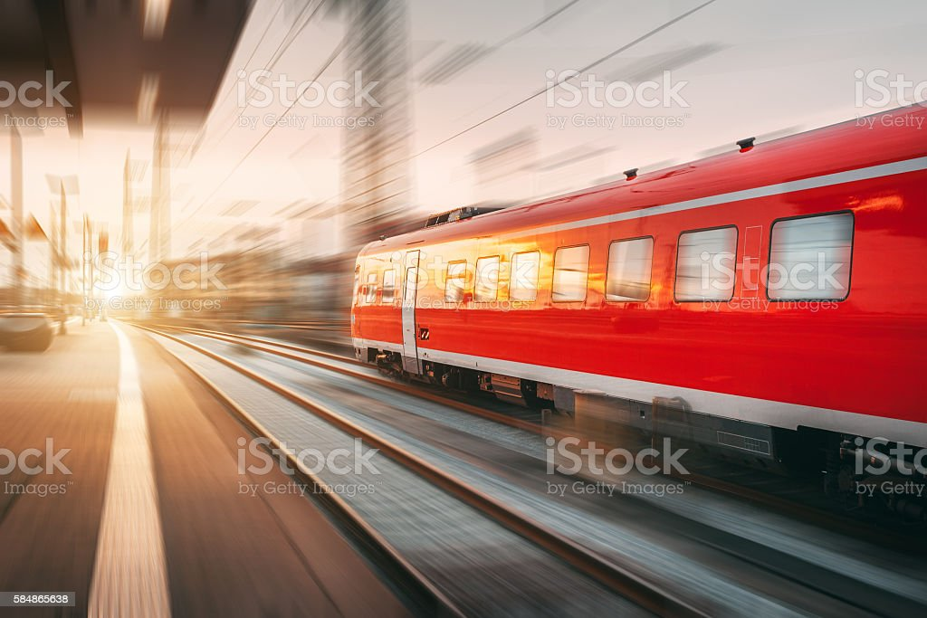 Modern high speed red passenger train at sunset. Railway station stock photo