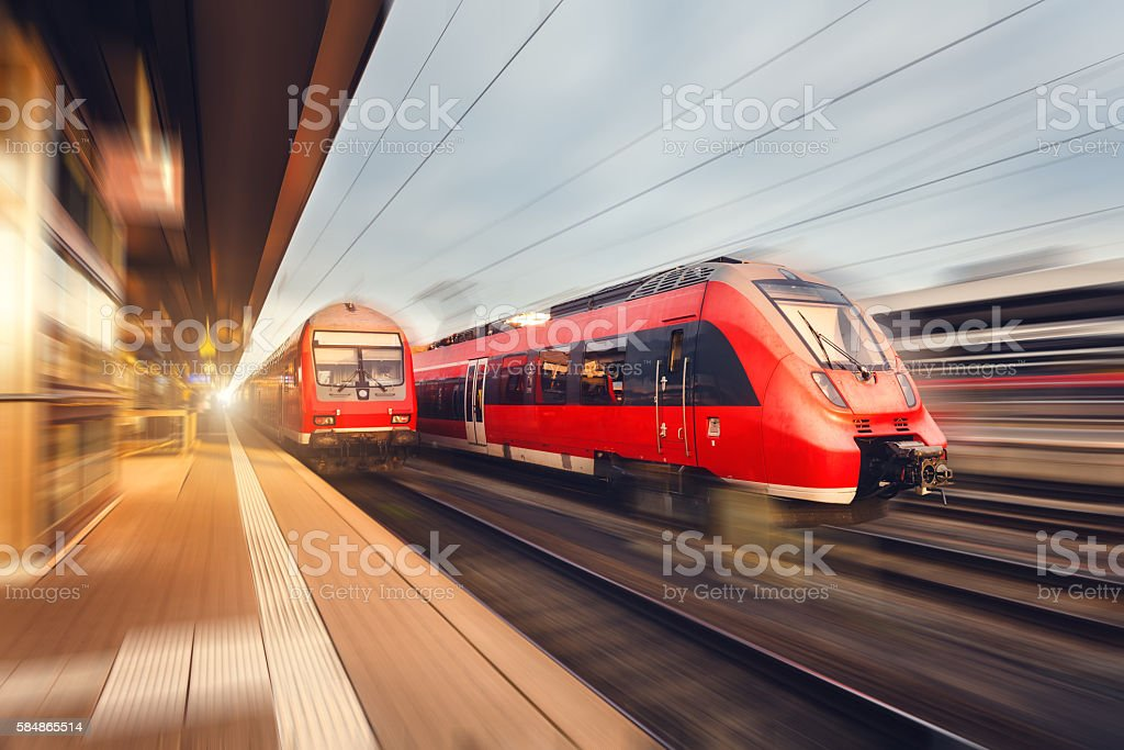 Modern high speed red passenger trains at sunset. Railway station stock photo