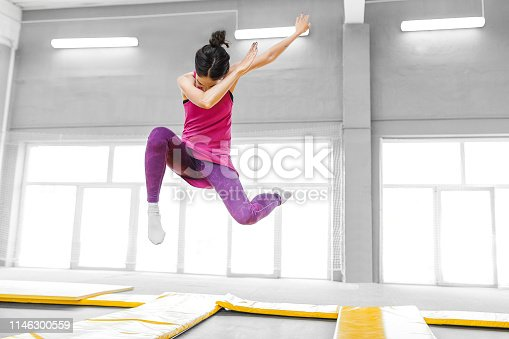 modern hip-hop woman dancer jumping and doing dab in trampoline fitness gym