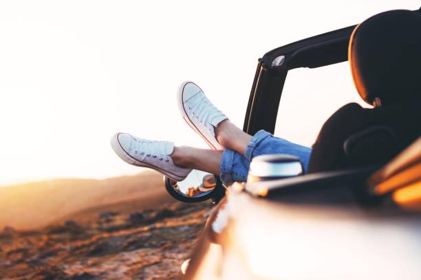 Moderne Hipster Mädchen ruhen im Cabrio und Aussicht bewundern. Frau Treiber Sonnenuntergang im Cabriolet stellt beide Füße auf Autotür – Foto