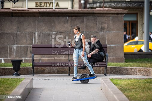 istock Modern hipster girl riding on an electric wheel 1226661556