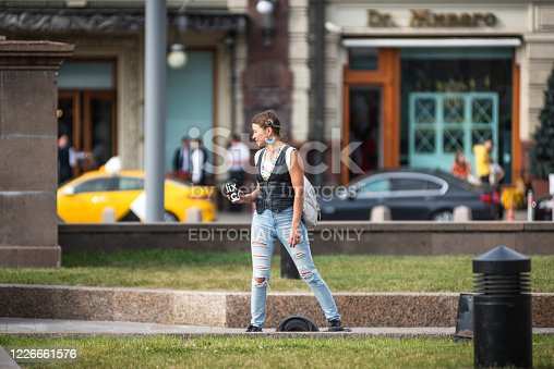 istock Modern hipster girl riding on an electric wheel 1226661576