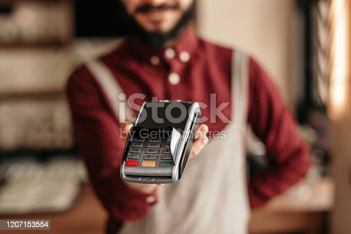 Crop friendly bearded man in uniform holding POS machine for payment with card with empty screen in restaurant