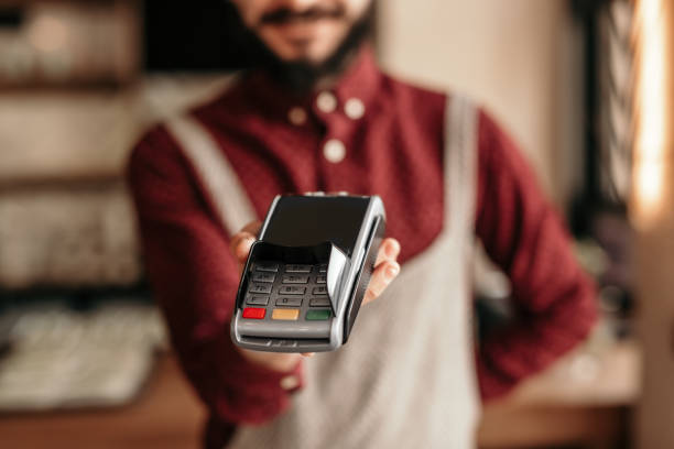 modern hipster waiter handing over payment terminal in cafe - paying with card contactless imagens e fotografias de stock