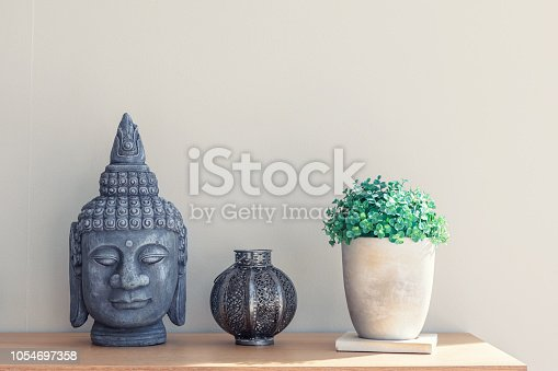 Modern decor on a shelf, a buddha head, a candle holder and a plastic plant in a pot.